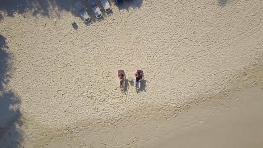 Aerial drone camera ascending above the couple in love lying in the sun on beach bed deck chairs and drinking cocktails at empty tropical white sand beach on atoll island resort with palm trees