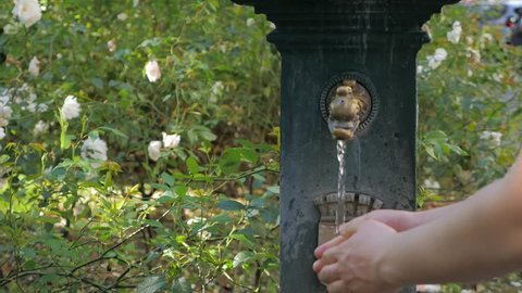 Man drinking water and washing hands from ancient oriental tap in the Milan, Italy. Hands under a stream of cool fresh water, outdoors in the summertime. Washing hands in natural green outdoor area.