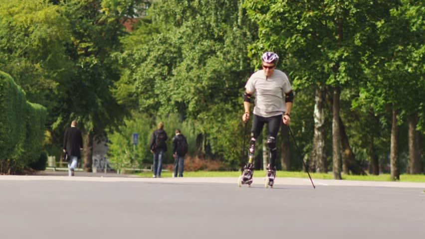Disabled skater in city park. Nordic skates. Slow motion shot.