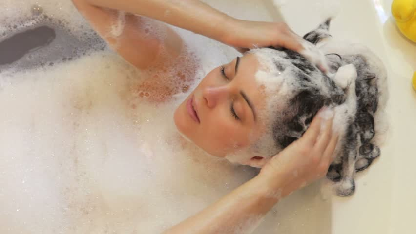 Relaxed woman lying in bubble filled bath washing her hair.