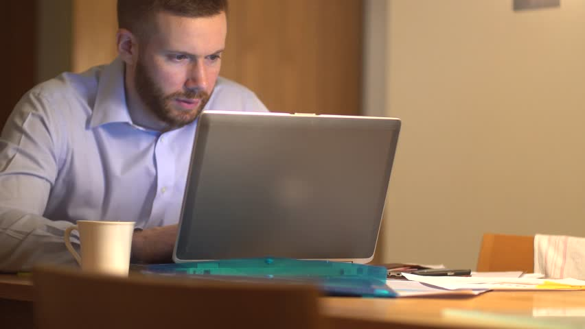 A young businessman is engaged in a telecommunications video call on a laptop. In the evening late at home. Handsome male in 30's, White Caucasian with a beard.