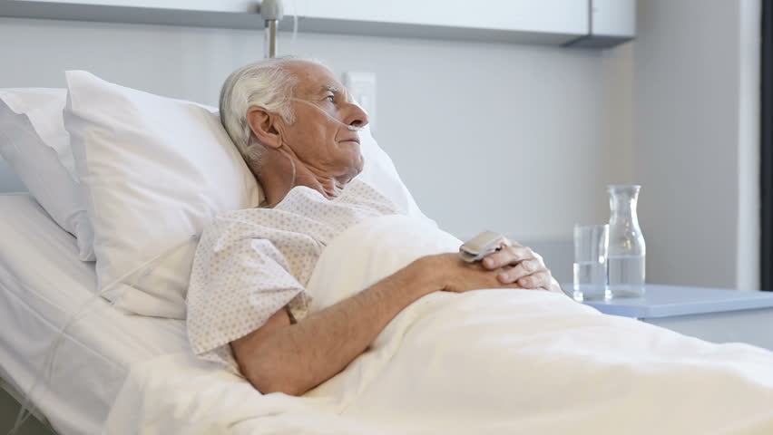 Sad senior man lying on hospital bed and looking away. Old patient with oxygen tube feeling lonely and thinking at hospital. Sick aged man lying hospitalized in a medical clinic. | Shutterstock HD Video #28765777