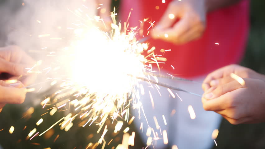 Closeup of the hands of a group of people, holding a burning Sparkler into the evening darkness. A group of people | Shutterstock HD Video #28784497