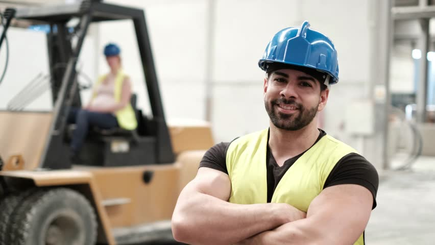 Young man posing and woman driving forklift in background