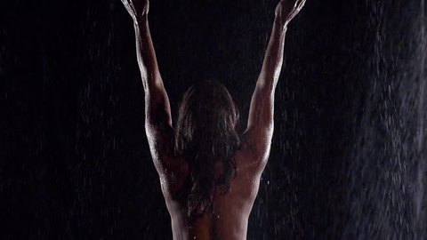 naked woman with long dark hair, stands in the rain, raised his hands. hands catches of the water jet. a spray of water. average plan. the view from the back. dark key