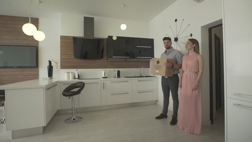 Happy young excited couple moving in new modern trendy apartment looking around beautiful interior design in 4k shot | Shutterstock HD Video #28852327