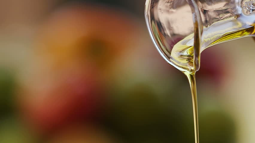 Slow motion shot of extra virgin olive oil being poured out a clear glass bottle | Shutterstock HD Video #28856737