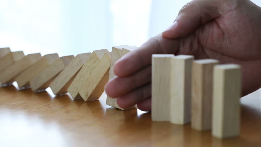 Male hand stopping the domino effect. Risk control concept