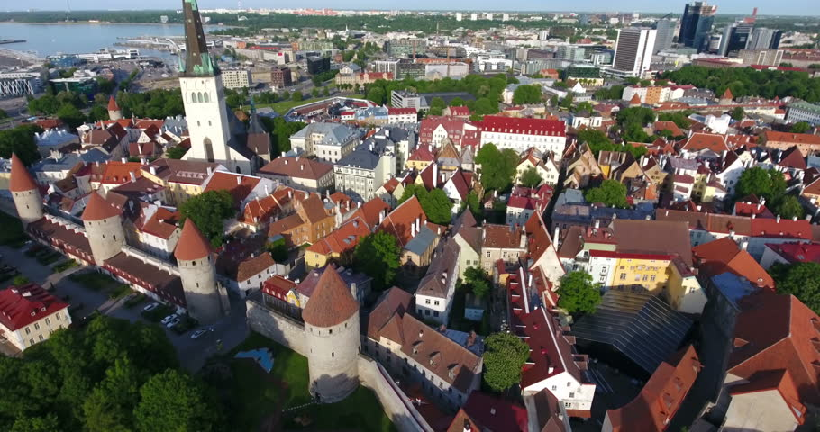 The tallest tower of the Old Town is a Saint Olaf church. Tiled roofs and strong walls of fortress. Estonia, Europe. Aerial view