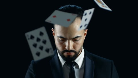 Close-up Portrait of a Bearded Man Looking at the Camera and Gaming Cards Raining on Him in Slow Motion. Shot with Black Background. Shot on RED EPIC-W 8K Helium Cinema Camera.