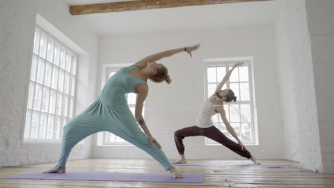 young sporty man and woman doing ashtanga yoga in studio, with wooden floor and big windows. Freedom, health and yoga concept. Dolly, slider