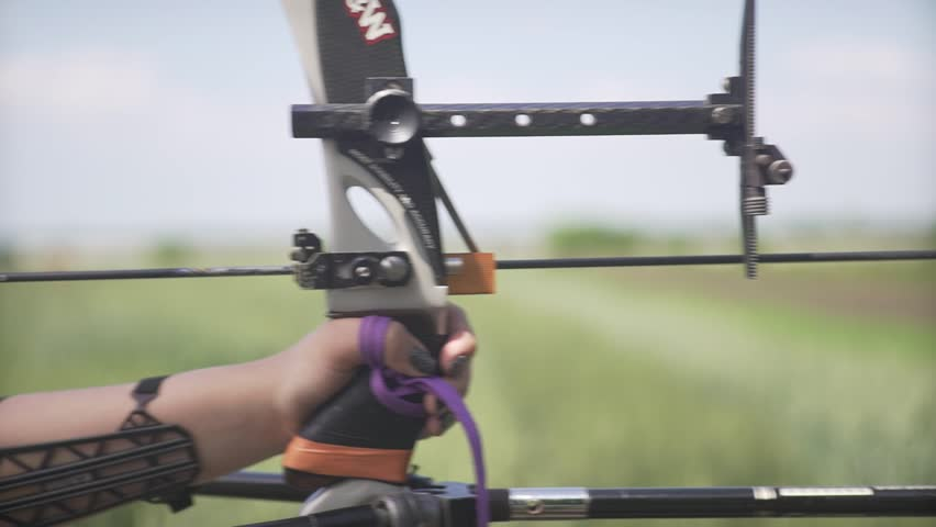 Close up shot of young attractive female pro archer with strong hands bending mechanic bow arrow concentrating on target