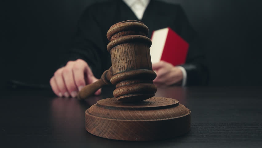 Male judge with law book in a courtroom striking the gavel | Shutterstock HD Video #28983907