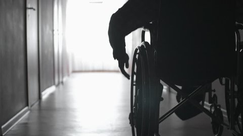 Tracking mid-section shot of silhouette of man turning wheels of wheelchair with hand and riding along dark corridor