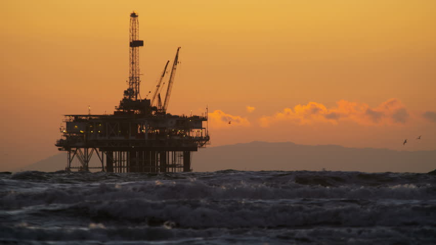 Deep sea offshore Industrial oil drilling platform in silhouette at sunset Pacific ocean California USA slow motion RED EPIC