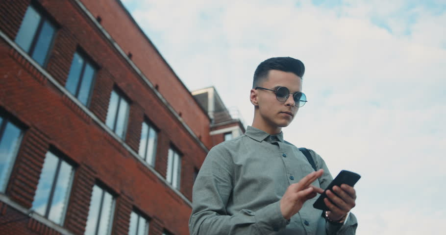 Young man boy standing street holding using phone checking student stylish brunette hipster round sunglasses device touching technology hairstyle shirt modern building tapping texting side view below | Shutterstock HD Video #29050357
