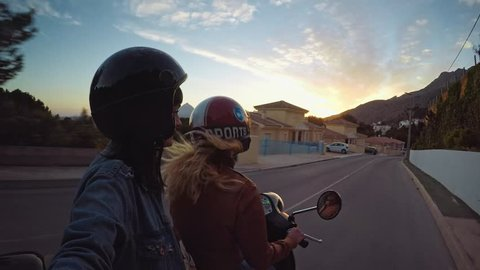 Two small teenager girls driving their scooter into sunset on small narrow road of mountain village in south of Spain. They are wearing their safe moto helmets and enjoy their ride