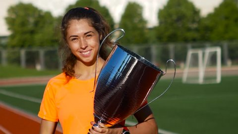 Beautiful girl with sport winner cup at stadium