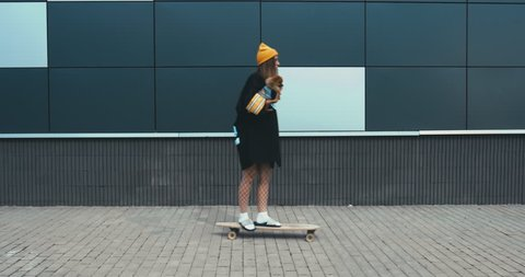 Young stylish Caucasian female riding longboard with her Pomeranian Spitz dog puppy outdoors. 4K UHD RAW edited footage