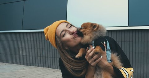 Young stylish Caucasian female playing with her Pomeranian Spitz dog puppy outdoors. 4K UHD RAW edited footage