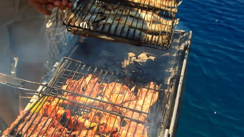 Barbecue fish on the boat. Dining experience on a blue cruise yacht, anchored, Gocek, Turkey. Preparation of food and barbeque itself; It is a commitment but the end results a party for your tastebuds