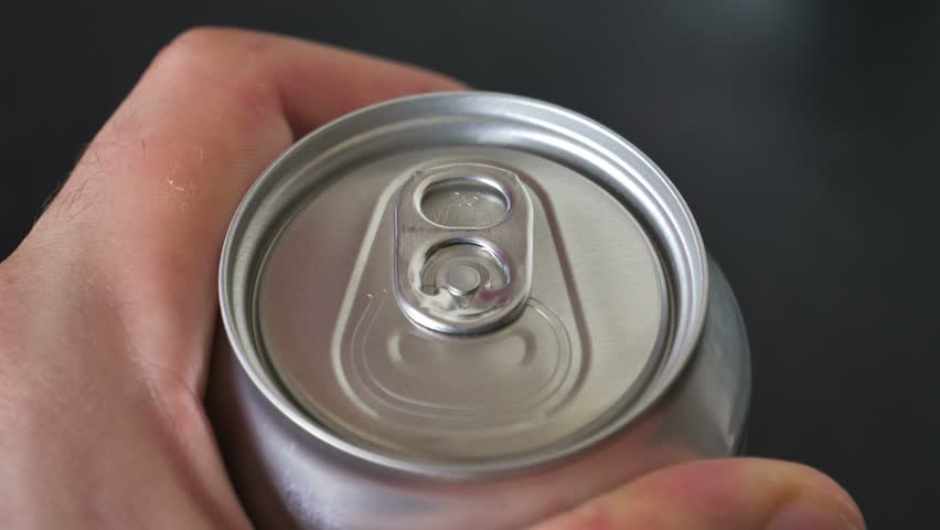 Male opening unmarked soda can of fizzy cola close up