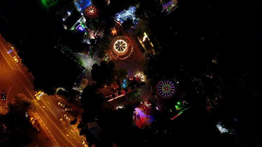 Shooting at altitude, the Park is lit at night with colored lights, Ferris wheel rides, night city road car lights | Shutterstock HD Video #29114407