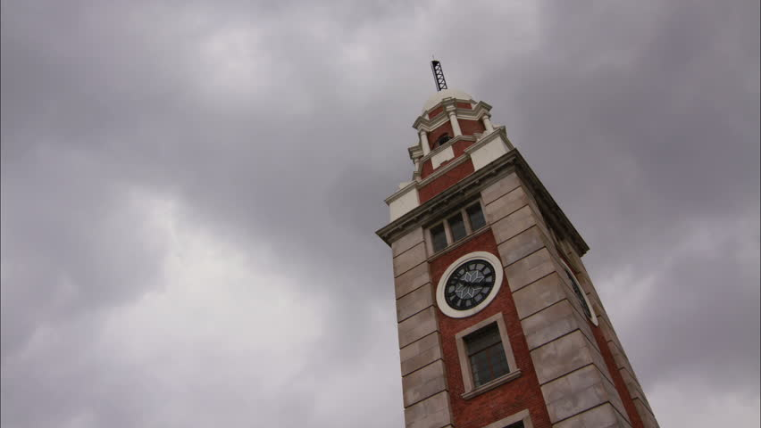 HONG KONG - The Clock Tower is a landmark in Hong Kong. It is located on the southern shore of Tsim Sha Tsui, Kowloon. Time lapse clouds shot with photo sequence using DSLR camera and combined in post