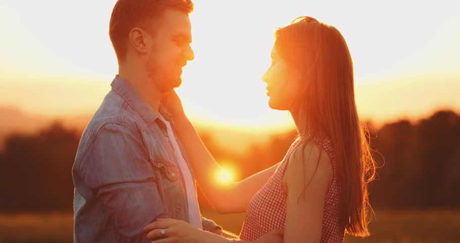 Young Couple Kissing at Sunset. SLOW MOTION 4K, Close Up. Romantic man and woman in love share a kiss. Love and affection. Cinematic backlit shot, Lens Flare.