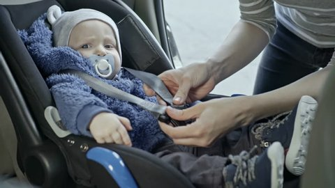 Tilt down of mother putting little baby into car seat and fastening belt