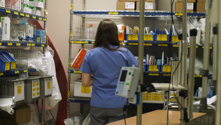 00e038290be 4k00:16A nurse collects medical supplies from a storage room in a