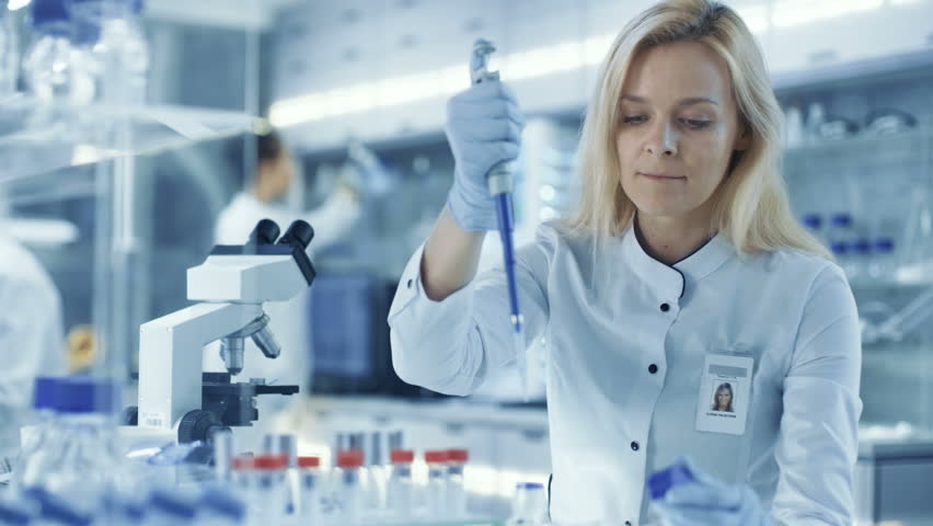 Female Research Scientist Uses Micropipette Filling Test Tubes. Scientist Work in a Big Laboratory/ Research Center. Shot on RED EPIC-W 8K Helium Cinema Camera.