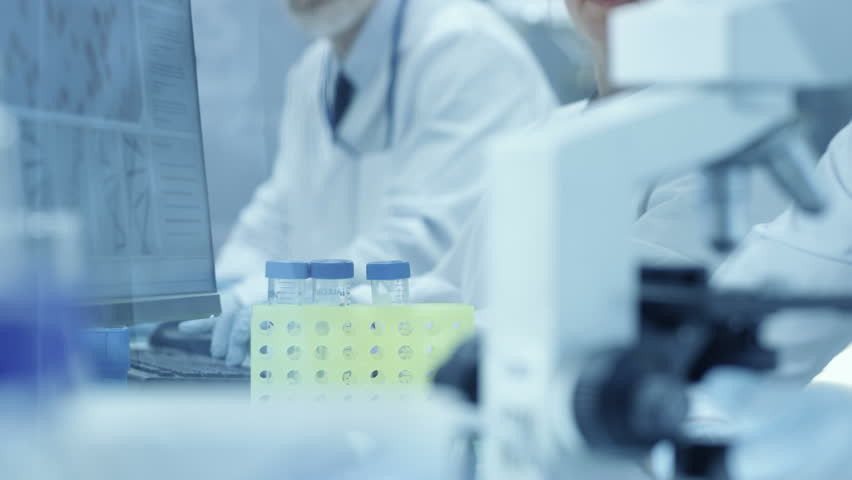 Medical Research Scientists Talks with Colleague and Looks at the Test Tube Results and Types Extracted Data into Her Computer. Scientists Work in a Modern Laboratory.  Shot on RED EPIC-W 8K Camera. | Shutterstock HD Video #29132683