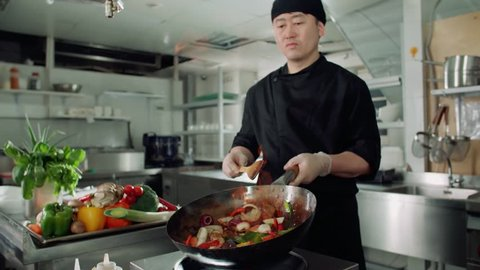 Asian chef works coloured mixed roasting vegetables in the wok with flame , kitchen Asian restaurant, slow motion