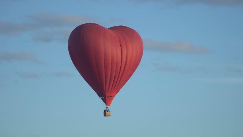 Hot air balloon in the shape of heart flies away.