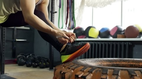 PAN of unrecognizable muscular woman in sportswear putting her legs on tire and tying shoelaces on sneakers at gym