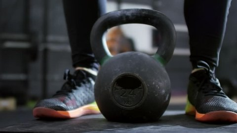 PAN with mid-section of unrecognizable sportswoman standing on step and doing kettlebell swings