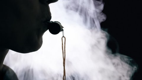 The smokey silhouette of a woman blowing into a whistle. Clear shape.