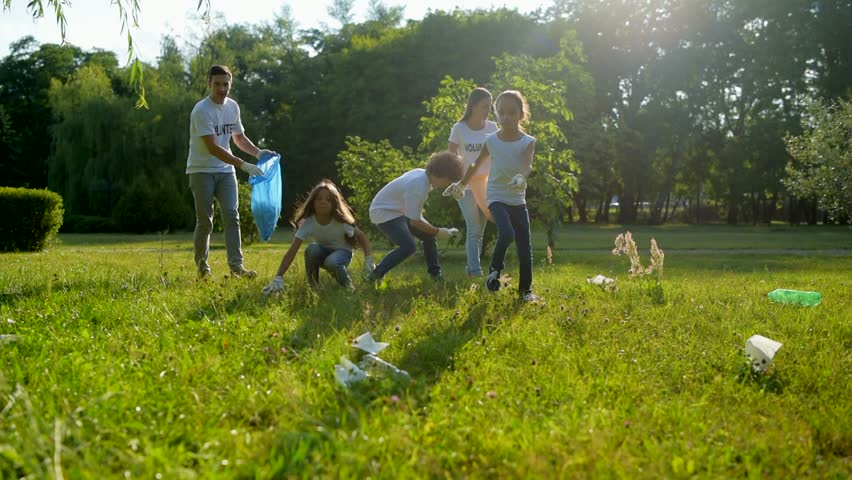 Mindful kids helping volunteers with picking up litter in park | Shutterstock HD Video #29187307