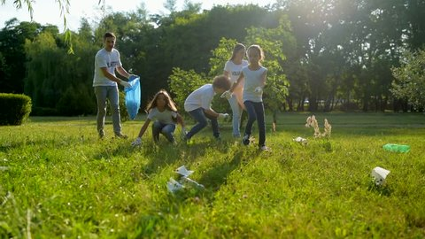 Mindful kids helping volunteers with picking up litter in park