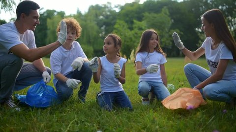 Cheerful kids helping volunteers with picking up plastic bottles outdoors