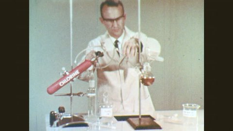 1960s: Man removes nozzle from chemical apparatus. Man introduces tubing to chemical apparatus. Hands adjust knob on compressed air nozzle.