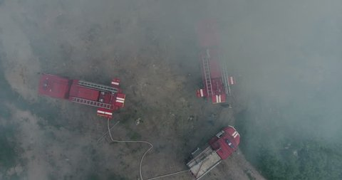 Top view from drone at the clouds of dense smoke poured in air and red fire-trucks on fireground.