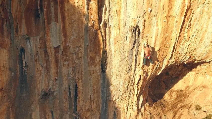 A man climbs on a steep rock in the sun