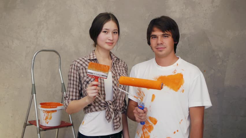 Attractive couple holding brushes and discussing remodeling flat