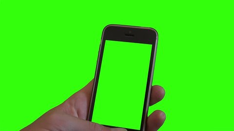 Holding Smartphone Over Green Screen. Hand holding a green screen smartphone over a green screen background