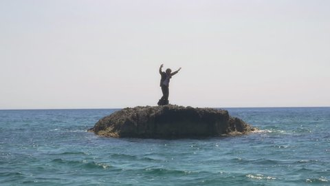 Man in suit whit a briefcase stranded on a deserted rock in the middle of the ocean waving his hands and moving around calling for help