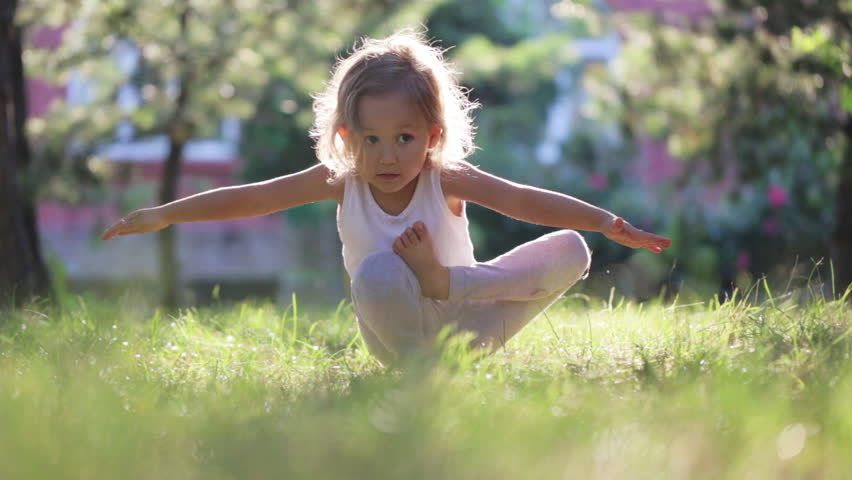 Little cute baby girl doing yoga exercise on the grass at beautiful sun light in green summer park. | Shutterstock HD Video #29255407