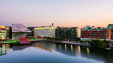 Dublin, Ireland. Aerial view of Grand Canal docks in Dublin, Ireland at sunrise. Empty streets and illuminated modern buildings, colorful clear sky. Time-lapse from night to day