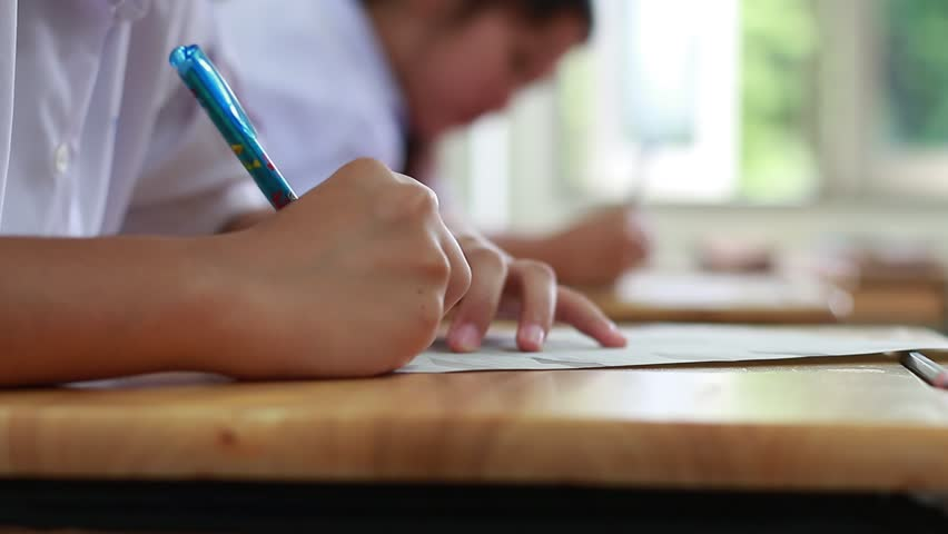 blurred of Female students school uniform Concentrating on doing tests, writing and taking exercises exams on wooden tables and chairs in secondary schools classroom Thailand, Educational concepts
